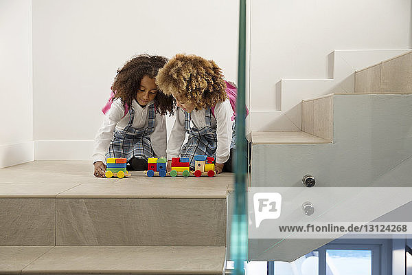 Sisters playing with toys on staircase
