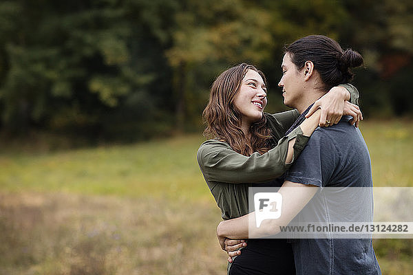 Couple embracing while standing on field