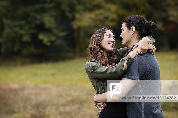 Paar umarmt sich  während es auf dem Feld steht