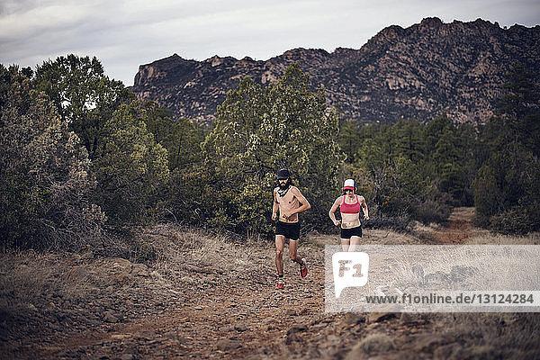 Sportliches Paar läuft auf Feld an Bergen vorbei