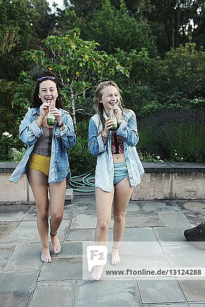 Fröhliche Freundinnen trinken Saft beim Spaziergang am Pool