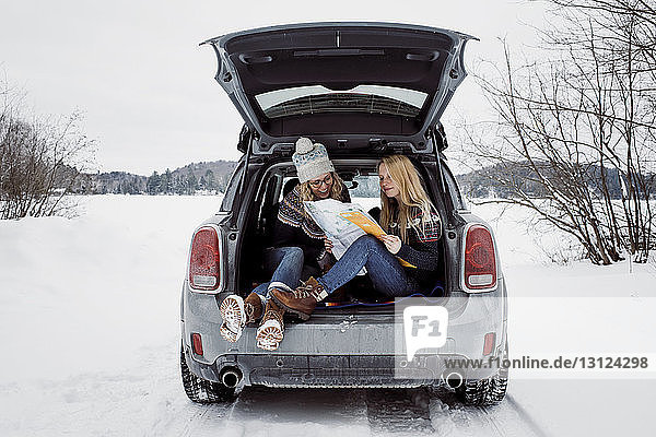 Happy female friends reading map while sitting in car trunk during winter