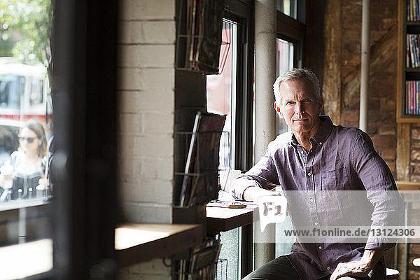 Porträt eines reifen Mannes am Tisch am Fenster im Café