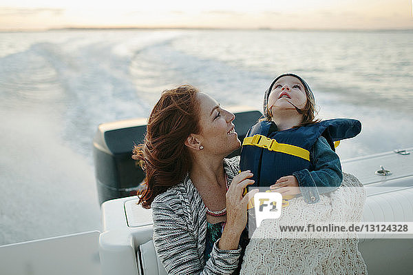 Girl looking up while traveling with mother on boat