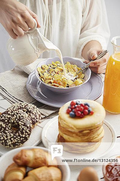 Mitschnitt einer Frau  die zu Hause Milch in Frühstückszerealien auf den Tisch schüttet