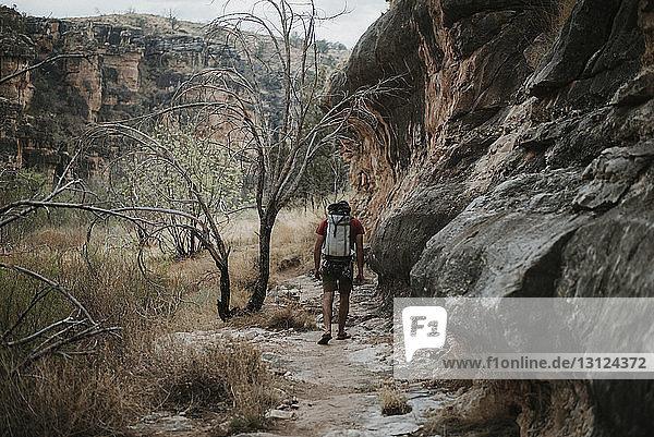 Rückansicht eines Mannes mit Rucksack beim Wandern durch Felsformationen im Wald