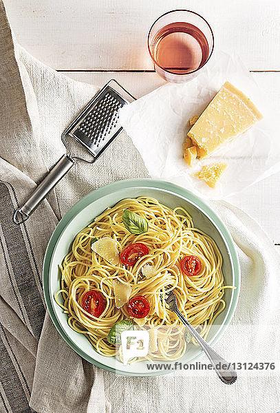 Schrägansicht auf Spaghetti  die im Teller serviert werden  mit Getränk und Käse auf dem Tisch