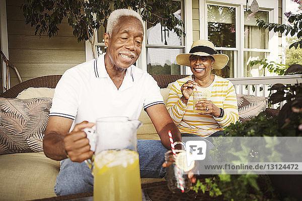 Glückliches älteres Ehepaar trinkt Limonade  während es auf der Veranda sitzt