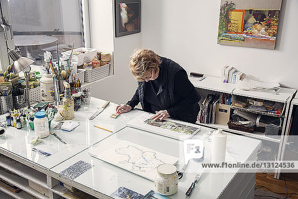 High angle view of senior woman drawing on table