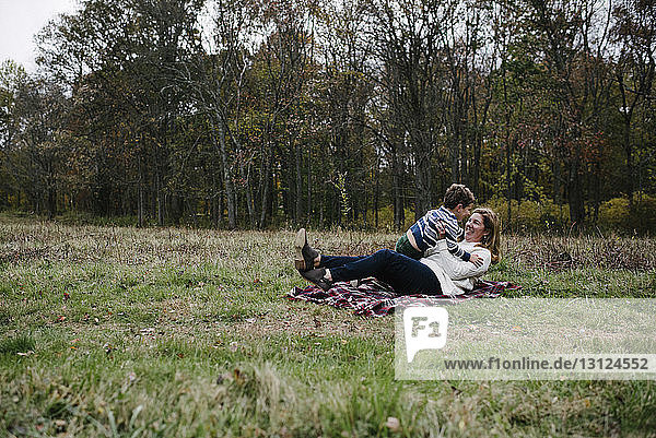 Mother playing with son while sitting on blanket at park