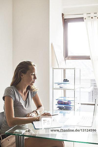Frau  die zu Hause am Laptop arbeitet