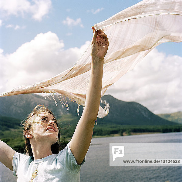 Beautiful woman holding scarf by lake and mountain against cloudy sky