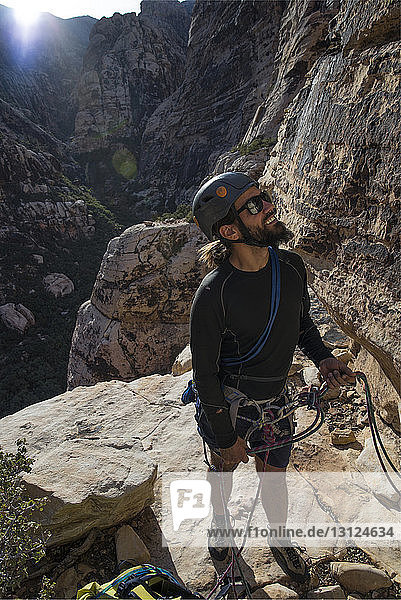 High angle view of rock climber looking up while standing on mountain