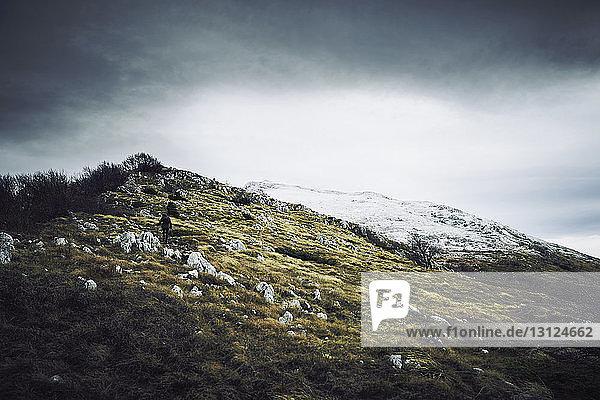 Rückansicht einer Frau  die im Winter auf einem Berg vor bewölktem Himmel wandert