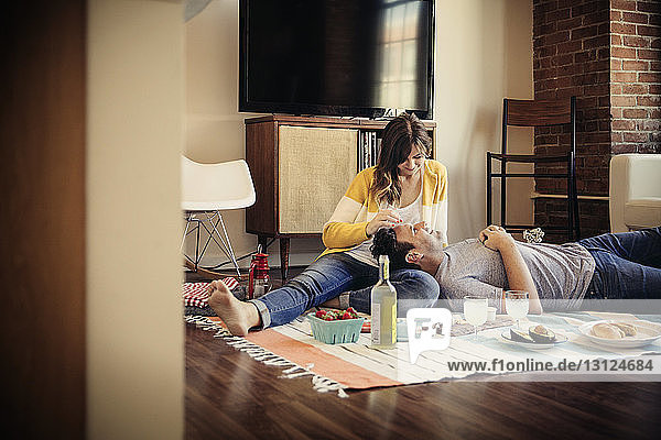 Glückliches Paar entspannt sich zu Hause auf Teppich