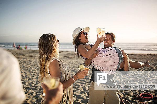 Fröhlicher Mann trägt Freundin mit Trinkglas am Strand