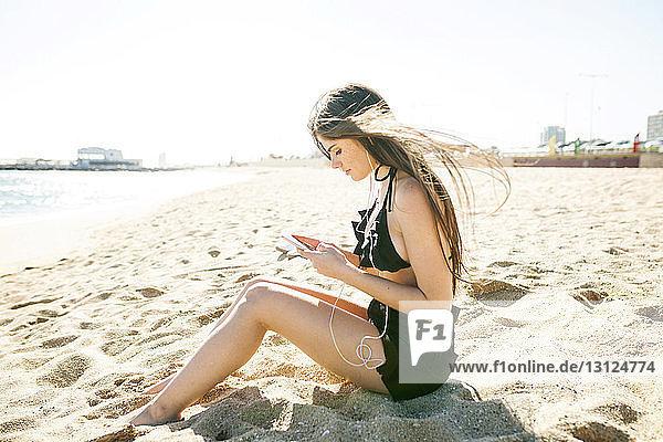 Seitenansicht einer jungen Frau  die telefoniert  während sie am Strand vor klarem Himmel sitzt