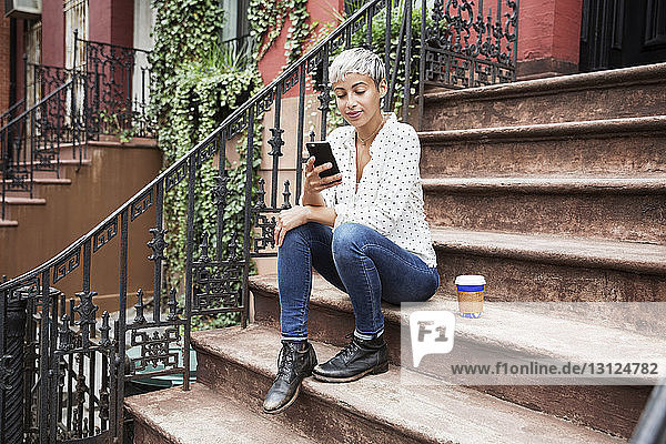 Woman using mobile phone while sitting on steps with coffee cup
