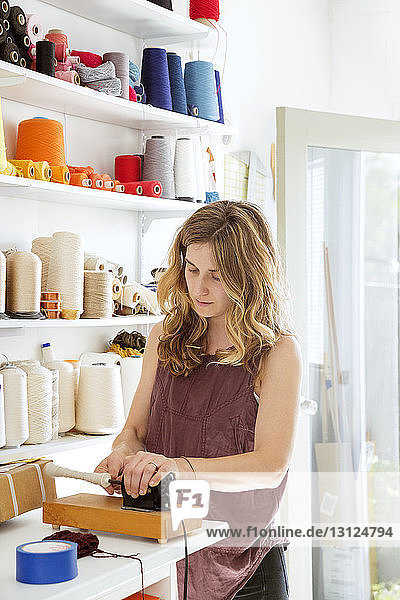 Frau spult Garn auf  während sie im Atelier steht