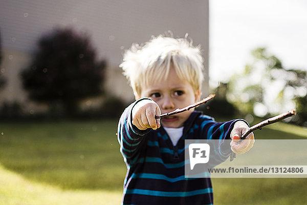 Junge spielt mit Stöcken im Hinterhof