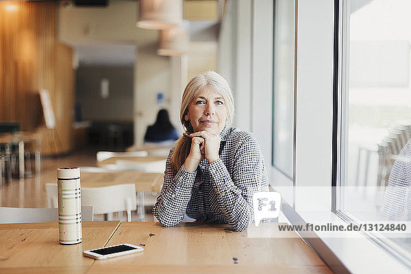 Portrait of businesswoman sitting at office cafeteria