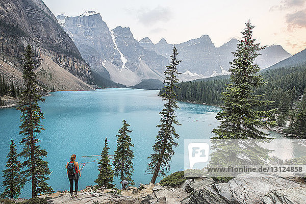 High angle view of woman standing on rocks by lake at Banff National Park