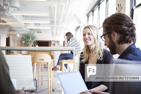Geschäftsmann mit Laptop-Computer bei der Planung mit Kollegen im Büro