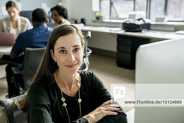 Porträt einer Geschäftsfrau  die am Schreibtisch sitzt  während Kollegen im Hintergrund diskutieren