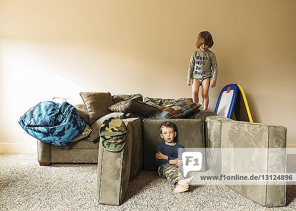 Portrait of boy relaxing while brother standing on sofa