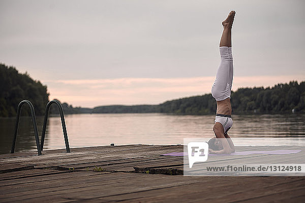 Woman practicing headstand on pier by lake against cloudy sky during sunset
