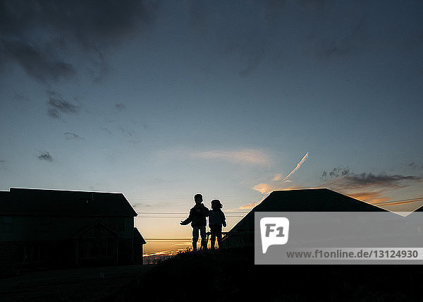Silhouette boys standing on roof against sky