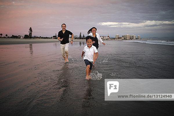 Glückliche Eltern rennen hinter ihrem Sohn am Strand gegen den bewölkten Himmel bei Sonnenuntergang