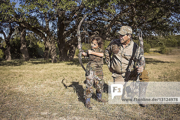 Girl aiming with arrow while father guiding on grassy field