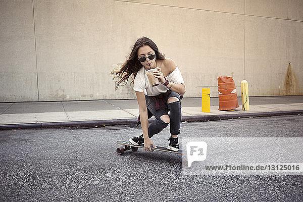 Junge Frau trinkt Saft beim Skateboarden auf der Straße