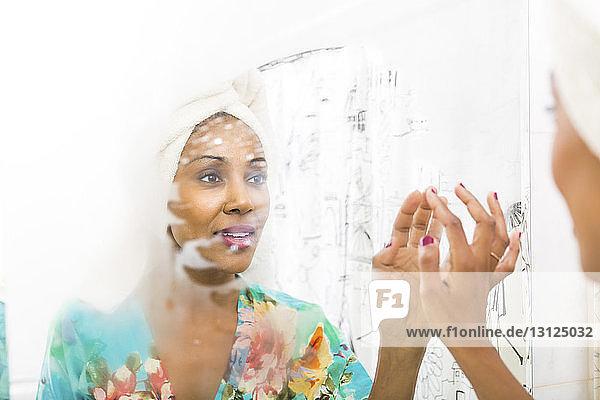 Frau trägt Handtuch auf dem Kopf  während sie die Reflexion im Spiegel betrachtet