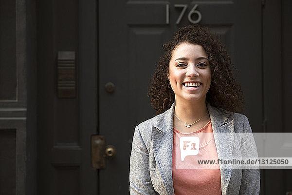 Porträt einer glücklichen Geschäftsfrau vor verschlossener Tür