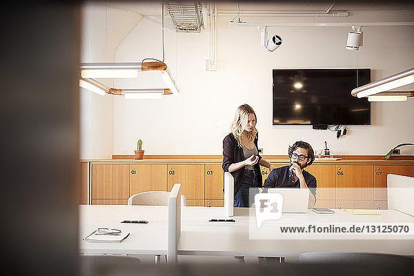 Geschäftsmann benutzt Laptop-Computer während einer Diskussion mit einer Mitarbeiterin im Büro