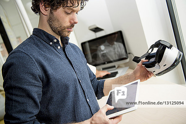 Engineer using tablet computer while examining virtual reality simulator in office