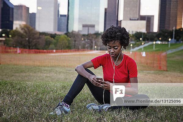 Frau hört Musik  während sie im Park telefoniert