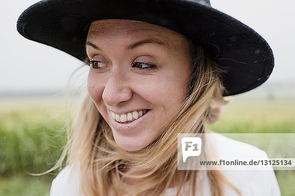 Close-up of happy woman wearing hat while standing against plants