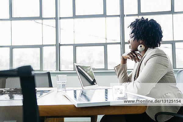 Seitenansicht einer nachdenklichen Geschäftsfrau  die neben einem Solarpanel-Modell auf dem Tisch sitzt