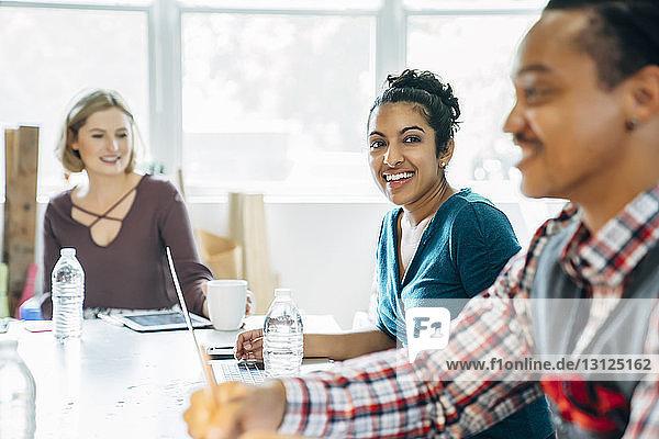 Glückliche Geschäftsfrau schaut weg  während sie bei ihren Kollegen sitzt