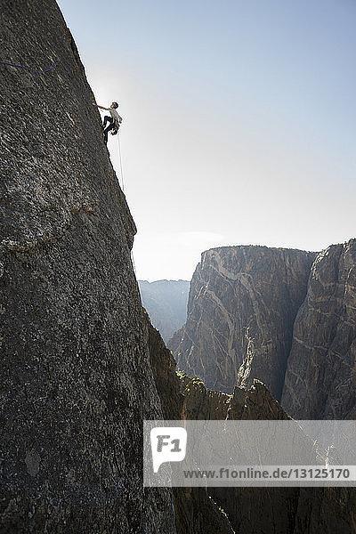 Niedrigwinkelansicht eines Mannes  der einen Berg gegen den Himmel besteigt