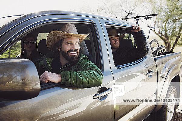 Fröhliche Freunde sitzen im Pick-up