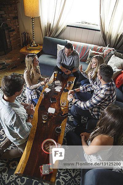 Hochwinkelaufnahme von Freunden beim Kartenspiel zu Hause