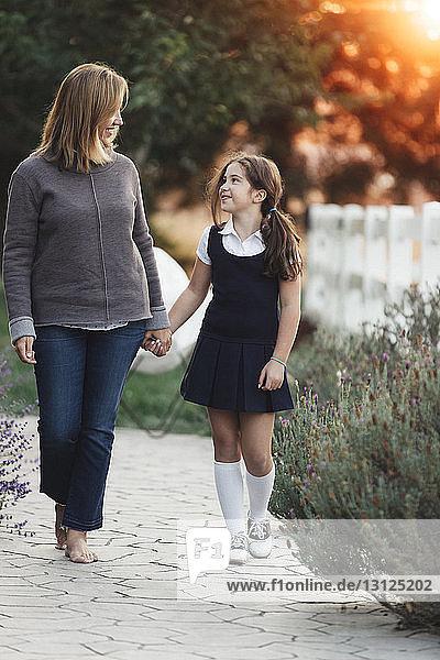 Mutter und Tochter halten sich beim Hofgang an den Händen