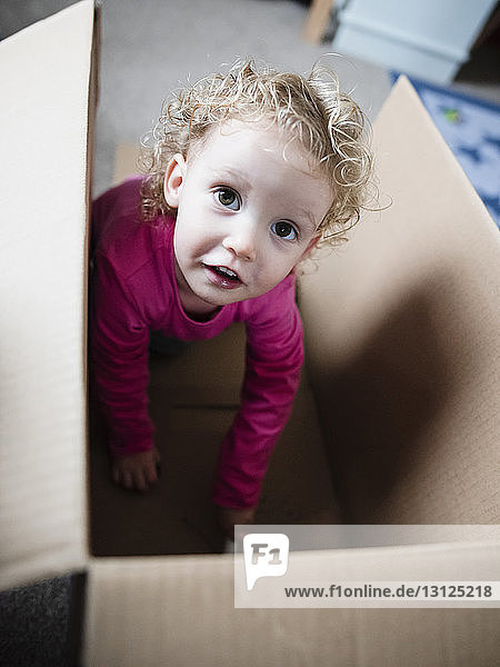 Portrait of playful girl sitting in cardboard box at home