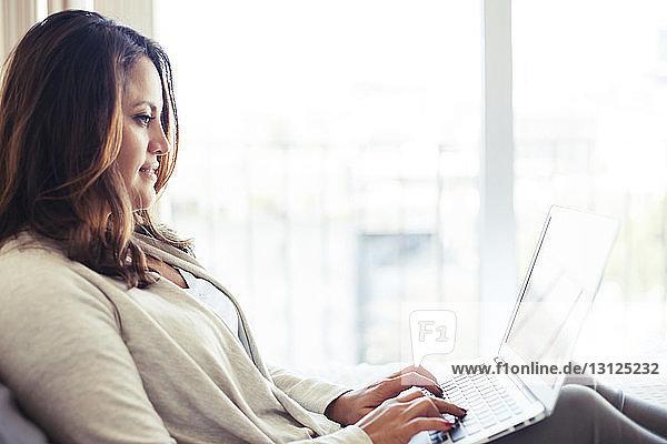 Seitenansicht einer Frau mit Laptop im Schlafzimmer