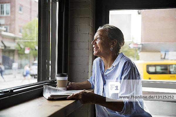 Lächelnde Frau mit Zeitung und Kaffee  die durch das Fenster am Tisch im Café schaut