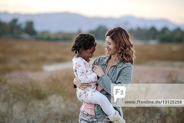 Lächelnde Mutter trägt Tochter  während sie auf Grasfeld im Wald steht